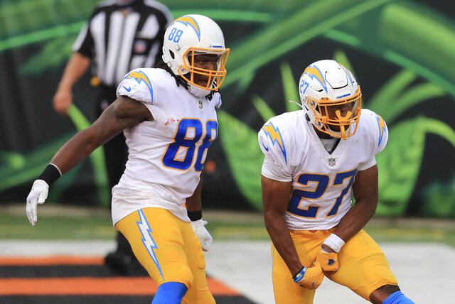 Los Angeles Chargers running back Joshua Kelley (27) celebrates with Virgil Green (88) after Kelley rushed for a touchdown during the second half of an NFL football game against the Cincinnati Bengals, Sunday, Sept. 13, 2020, in Cincinnati. (AP Photo/Aaron Doster)