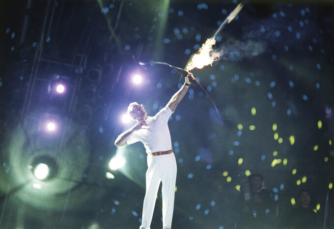 An arrow carrying the Olympic flame leaves the bow of Antonio Rebollo to light the Olympic Torch and open the XXV Olympic in Barcelona Saturday night, July 25, 1992. (AP Photo/ Dominique Mollard)