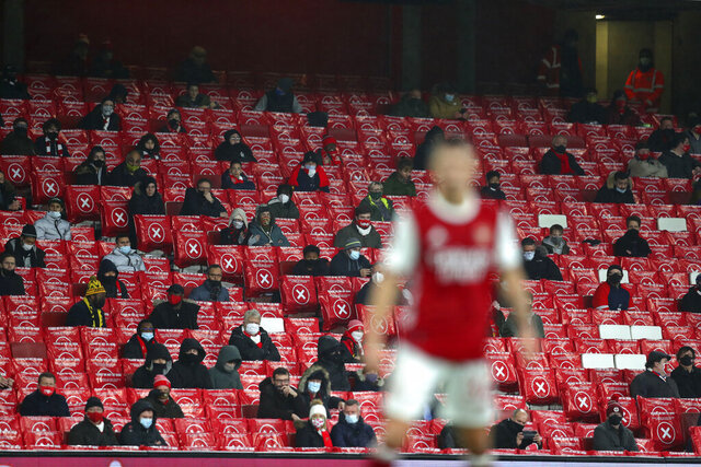 Arsenal fans sit in spaced out seats for coronavirus rules during an English Premier League soccer match between Arsenal and Burnley at the Emirates stadium in London, England, Sunday Dec. 13, 2020. (Catherine Ivill/Pool via AP)