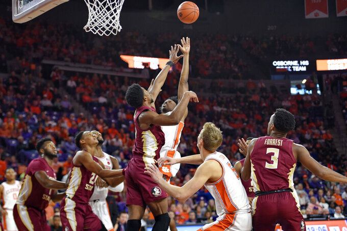 Clemson's John Newman lll, center right, shoots while defended by Florida State's Malik Osborne, center left, during the first half of an NCAA college basketball game Saturday, Feb. 29, 2020, in Clemson, S.C. (AP Photo/Richard Shiro)