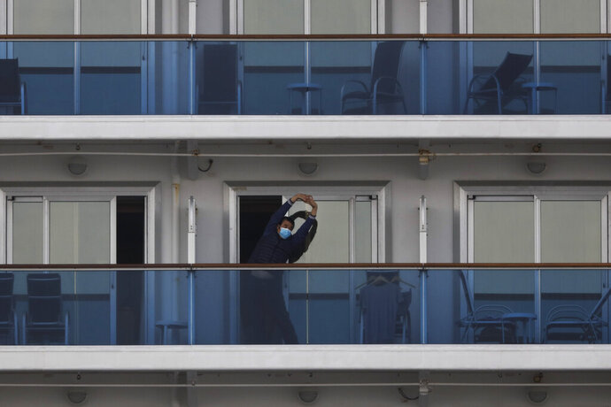 A quarantined passenger on the Diamond Princess cruise ship stretches on the balcony of his cabin Saturday, Feb. 15, 2020, in Yokohama, near Tokyo. A viral outbreak that began in China has infected more than 67,000 people globally. The World Health Organization has named the illness COVID-19, referring to its origin late last year and the coronavirus that causes it. (AP Photo/Jae C. Hong)