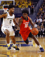 Illinois guard Andres Feliz (10) drives on Michigan guard David DeJulius (0) during the first half of an NCAA college basketball game, Saturday, Jan. 25, 2020, in Ann Arbor, Mich. (AP Photo/Carlos Osorio)
