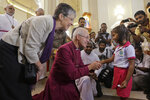 The Archbishop of Canterbury Justin Welby blesses a survivor of the Easter Sunday attack at St. Sebastian's church in Katuwapitiya village, Negombo , Sri Lanka, Thursday, Aug. 29, 2019. The figurehead of the Church of England emphasized the need for Christian unity on Thursday as he paid tribute to the victims of the Easter Sunday bomb attacks at a Roman Catholic church in Sri Lanka. A total of 263 people were killed when seven suicide bombers from a local Muslim group attacked three churches and three luxury hotels on April 21. (AP Photo/Eranga Jayawardena)