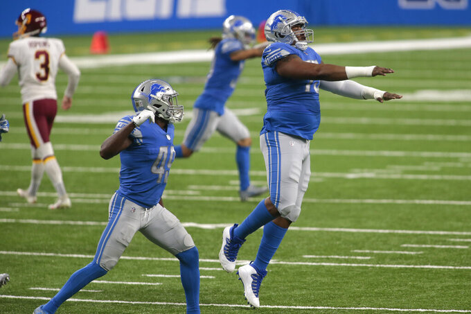 Detroit Lions safety C.J. Moore (49) and defensive end Frank Herron (75) celebrate a missed field goal by Washington Football Team kicker Dustin Hopkins (3) during the first half of an NFL football game, Sunday, Nov. 15, 2020, in Detroit. (AP Photo/Tony Ding)