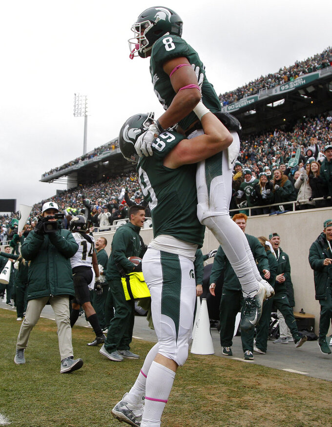 Michigan State's Jalen Nailor (8) is lifted by Matt Dotson as they celebrate Nailor's touchdown against Purdue during the fourth quarter of an NCAA college football game, Saturday, Oct. 27, 2018, in East Lansing, Mich. Michigan State won 23-13. (AP Photo/Al Goldis)