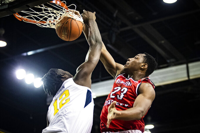 FILE - In this Nov. 16, 2018, file photo, Western Kentucky center Charles Bassey (23) dunks over West Virginia Mountaineers forward Andrew Gordon (12) an NCAA college basketball game at the Myrtle Beach Invitational in Conway, S.C. Bassey enters this season as one of the top pro prospects from any college that isn't in a major conference or in the preseason Top 25. (Austin Anthony/Daily News via AP, File)