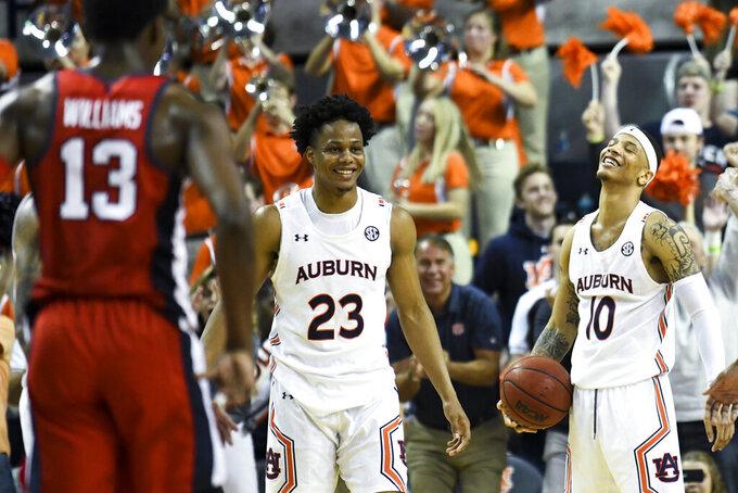 Auburn forward Isaac Okoro (23) and guard Samir Doughty (10) celebrate the final rebound against Mississippi in an NCAA college basketball game Tuesday, Feb. 25, 2020, in Auburn, Ala. (AP Photo/Julie Bennett)