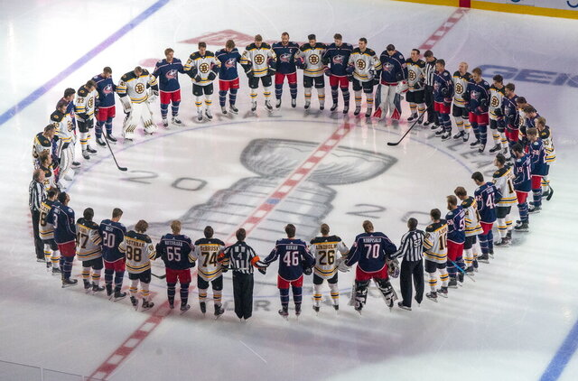 The Boston Bruins and the Columbus Blue Jackets stand together for the national anthems prior to NHL hockey exhibition game action in Toronto, Thursday, July 30, 2020. (Frank Gunn/The Canadian Press via AP)