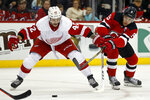Detroit Red Wings right wing Martin Frk (42) battles for the puck with New Jersey Devils left wing Taylor Hall (9) during the second period of an NHL hockey game Saturday, Nov. 17, 2018, in Newark, N.J. (AP Photo/Adam Hunger)
