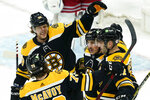 Boston Bruins right wing David Pastrnak (88), defenseman Charlie McAvoy (73), and center Brad Marchand (63) gather to celebrate a goal by center Patrice Bergeron, right, in the first period of an NHL hockey game against the New York Rangers, Thursday, May 6, 2021, in Boston. (AP Photo/Elise Amendola)