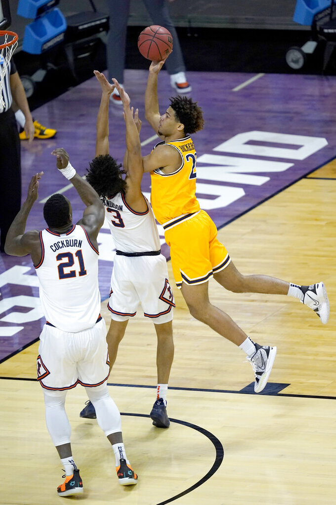 Drexel's T.J. Bickerstaff, right, shoots over Illinois 's Jacob Grandison (3) and Kofi Cockburn, during the first half of a first round NCAA college basketball tournament game Friday, March 19, 2021, at the Indiana Farmers Coliseum in Indianapolis .(AP Photo/Charles Rex Arbogast)