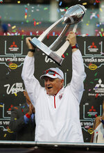 Fresno State head coach Jeff Tedford holds up the trophy after his team defeated Arizona State in the Las Vegas Bowl NCAA college football game, Saturday, Dec. 15, 2018, in Las Vegas. (AP Photo/John Locher)