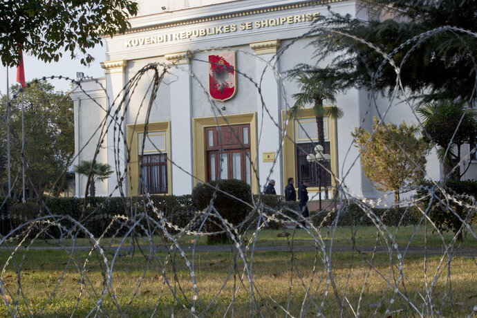 Policemen are seen behind barbwire placed to secure the Parliament building as opposition supporters gather to participate in an anti-government rally in capital Tirana, Albania, on Tuesday, Feb. 21, 2019.  Albania's opposition supporters have surrounded the parliament building Thursday, asking for the resignation of the government which they allege is corrupt. (AP Photo/Visar Kryeziu)
