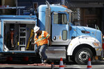 In this photo taken Aug. 15, 2019, a Pacific Gas & Electric worker exits a truck in San Francisco. Pacific Gas and Electric Co. bondholders and wildfire victims have joined forces and proposed their own reorganization plan as they try to wrest control of the bankrupt company from its stockholders. The San Francisco Chronicle reports the two groups told PG&E's bankruptcy judge Thursday, Sept. 19, 2019, their proposal would include a $24 billion settlement to pay everyone owed money because of fires started by the company's power lines in recent years. (AP Photo/Jeff Chiu)