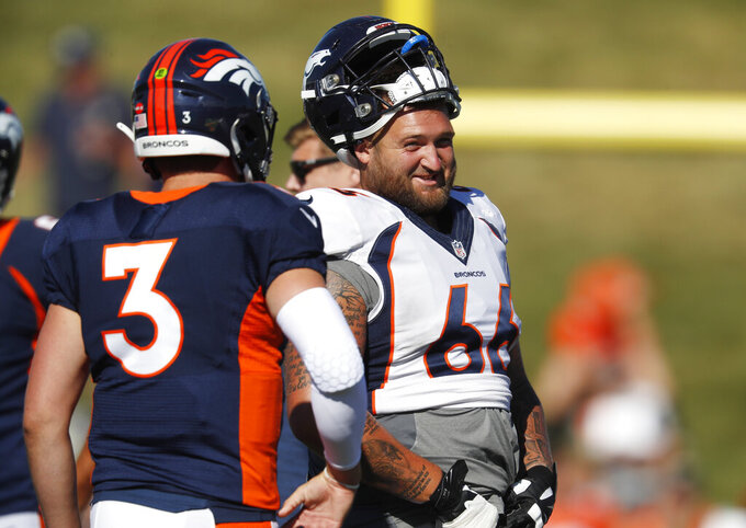 Denver Broncos offensive tackle Dalton Risner, back, jokes with quarterback Drew Lock as they take part in an NFL football training camp session Monday, Aug. 5, 2019, in Englewood, Colo. (AP Photo/David Zalubowski)
