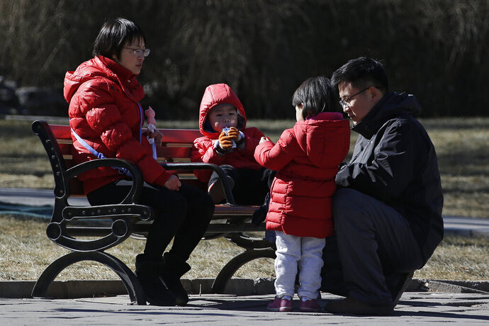 In this Feb. 17, 2019, photo, a couple spend time with their children at a park in Beijing. Facing a future demographic crisis and aging society, China's leaders are desperately seeking to persuade couples to have more children. But the country's bureaucrats don't seem to have gotten the message, fining a couple in a recent widely publicized case for having a third child against the strict letter of the law. (AP Photo/Andy Wong)