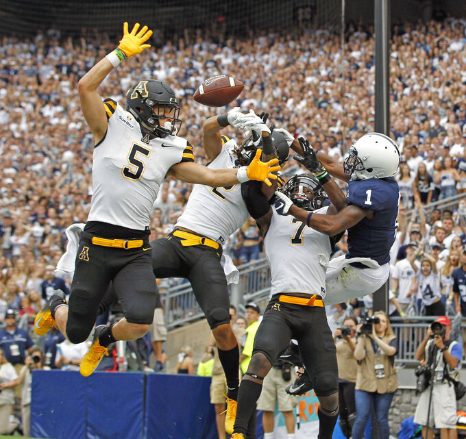 FILE - In this Sept. 1, 2018, file photo, Appalachian State defenders Thomas Hennigan (5), Corey Sutton (2) and Josh Thomas (7), break up a pass intended for Penn State's KJ Hamler (1) in the end zone during the first half of an NCAA college football game, in State College, Pa. Bolstered by its first Top 25 ranking in the history of its program, No. 25 Appalachian State will face longtime rival Georgia Southern in a Sun Belt showdown on Thursday night.  (AP Photo/Chris Knight, File)