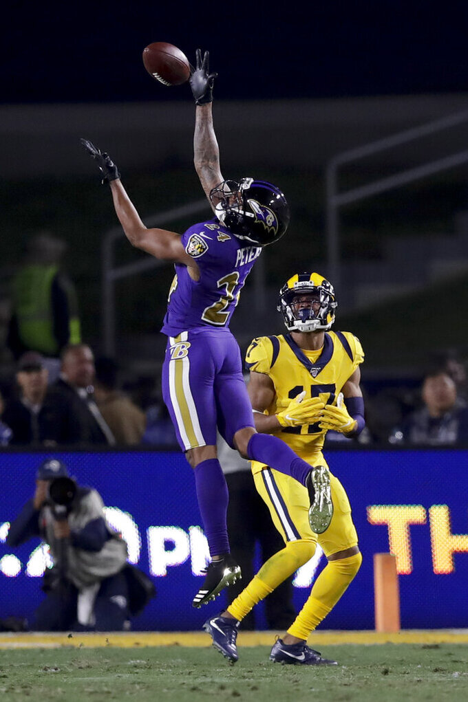 Baltimore Ravens cornerback Marcus Peters intercepts a pass intended for Los Angeles Rams wide receiver Robert Woods during the second half of an NFL football game Monday, Nov. 25, 2019, in Los Angeles. (AP Photo/Marcio Jose Sanchez)
