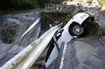 A vehicle falls off collapsed road in the typhoon-hit Kakuda city, Miyagi prefecture, northern Japan,  Sunday, Oct. 13, 2019. Rescue efforts for people stranded in flooded areas are in full force after a powerful typhoon dashed heavy rainfall and winds through a widespread area of Japan, including Tokyo.(Kyodo News via AP)