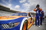 Brad Keselowski puts on a helmet before a NASCAR Cup Series auto race at Atlanta Motor Speedway, Sunday, June 7, 2020, in Hampton, Ga. (AP Photo/Brynn Anderson)