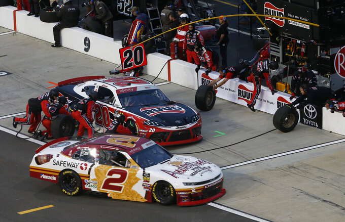 Tyler Reddick (2) heads into the pits as Christopher Bell (20) makes a pits stop during the NASCAR Xfinity Series auto race at Richmond Raceway in Richmond, Va., Friday, April 12, 2019. (AP Photo/Steve Helber)