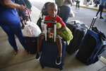 3-year-old Hurricane Dorian evacuee Trevanti Saunders of Freeport, sits on a suitcase with his family as they wait for a ride after arriving on the Grand Celebration cruise ship from Freeport, a city in the Grand Bahamas on Wednesday, Sept. 18, 2019 in Riviera Beach. The cruise ship transported hundreds of evacuees seeking passage from Freeport after the damaged caused by Hurricane Dorian. Saunders mother, Denise Saunders, said