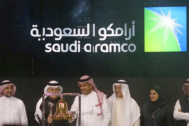 FILE - In this Dec. 11, 2019, file photo, executives of the Saudi Arabia's state-owned oil company Aramco and stock market officials celebrate the debut of Aramco's initial public offering on the Riyadh's stock market, in Saudi Arabia. On Tuesday, May 12, 2020, Saudi Aramco announced a net income of $16.7 billion for the first three months of the year and dividends of $18.75 billion for shareholders. Despite posting the highest quarter dividends in 2020 of any listed company, its profits were 25% down compared to the same time last year. (AP Photo/Amr Nabil, File)