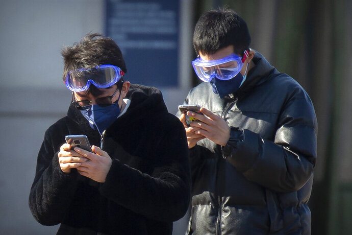 Travelers wear face masks and goggles as they use their smartphones outside the Beijing Railway Station in Beijing, Saturday, Feb. 15, 2020. People returning to Beijing will now have to isolate themselves either at home or in a concentrated area for medical observation, said a notice from the Chinese capital's prevention and control work group published by state media late Friday. (AP Photo/Mark Schiefelbein)