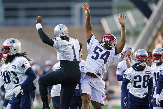 New England Patriots quarterback Cam Newton (1) and outside linebacker Dont'a Hightower (54) jump in greeting at Gillette Stadium during NFL football practice Friday, Aug. 6, 2021, in Foxborough, Mass. (AP Photo/Elise Amendola)