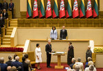 Lithuanian President-elect Gitanas Nauseda, centre left, flanked by his wife Diana Nausediene, left, takes the oath of office during his inauguration ceremony in the Lithuanian parliament in Vilnius, Lithuania, Friday, July 12, 2019.  Former bank analyst Nauseda has been sworn in as Lithuania's president taking the lead of the Baltic country of 3 million. (AP Photo/Mindaugas Kulbis)