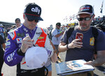 Jimmie Johnson gives an autograph after practice for a NASCAR auto race Friday, Aug. 30, 2019, in Darlington, S.C.. (AP Photo/Terry Renna)