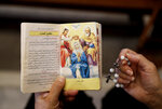 A Lebanese woman reads a religious book during Sunday Mass at Saint Maron-Baouchrieh Church that was damaged by last Tuesday's explosion that hit the Beirut seaport, in Baouchrieh neighborhood in Beirut, Lebanon, Sunday, Aug. 9, 2020. In interviews with The Associated Press, Father Rabih Thoumy and church priest Father Marwan Mouawad recount the horror of the moment the blast rocked the church. Thoumy says: