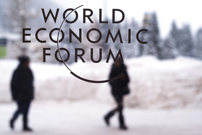 FILE - In this Sunday, Jan. 21, 2018 file photo, two people walk behind the logo of the World Economic Forum at the meeting's conference center in Davos, Switzerland. After a two-year hiatus due the coronavirus pandemic, organizers of the annual Davos conference will host the high-profile gathering of elites in the Swiss Alps in-person again in January. The World Economic Forum said its next annual meeting will take place from Jan. 17-22, 2022 in the resort of Davos in eastern Switzerland. (AP Photo/Markus Schreiber, file)