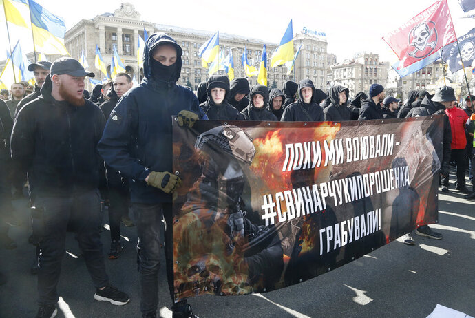 Far-right demonstrators attend rally against corruption in downtown Kiev, Ukraine, Saturday, March 23, 2019. The placard reads