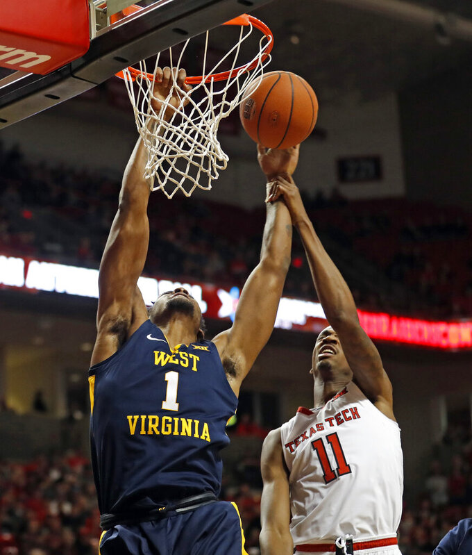 Texas Tech's Tariq Owens (11) fouls West Virginia's Derek Culver (1) as he shoots the ball during the first half of an NCAA college basketball game Monday, Feb. 4, 2019, in Lubbock, Texas. (AP Photo/Brad Tollefson)