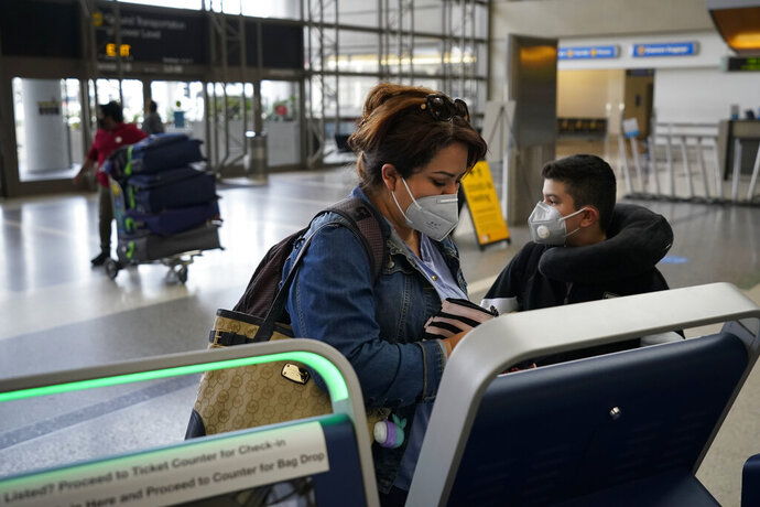 Esmeralda Elizalde checks in for her flight to Mexico at the Los Angeles International Airport in Los Angeles, Monday, Nov. 23, 2020. About 1 million Americans a day packed airports and planes over the weekend even as coronavirus deaths surged across the U.S. and public health experts begged people to stay home and avoid big Thanksgiving gatherings. (AP Photo/Jae C. Hong)