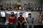 Young soccer players, from left, Daniel Rocaro, Uriel Lopez, and Bauti Fernandez pose for a photo in front of their trophies during an interview at their club
