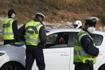 Policemen check the drivers for valid documents at a roadblock in Elefsina toll stations, west of Athens, Wednesday, April 28, 2021. Greek police set up checkpoints along highways leading out of the Greek capital to enforce a travel ban tightened for Orthodox Easter on May 2. Easter holidays are often celebrated with relatives outside Athens and other cities, but the government said COVID-19 infection levels remain too high to allow free travel. (AP Photo/Thanassis Stavrakis)