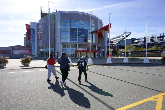 Football fans walk toward the Patriots ProShop at Gillette Stadium, Sunday, Oct. 11, 2020, in Foxborough, Mass. The NFL has postponed the Denver Broncos-New England Patriots football game due to another positive coronavirus test with the Patriots.  (AP Photo/Steven Senne)