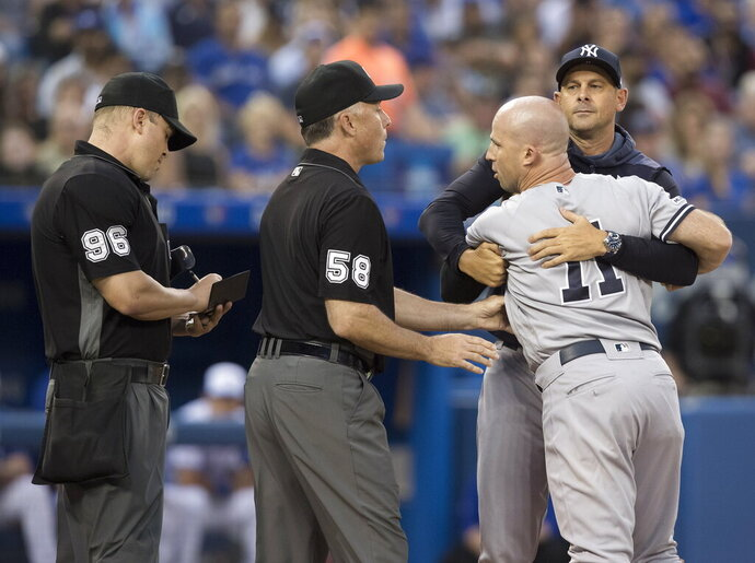 New York Yankees manager Aaron Boone, back right, holds Brett Gardner back from getting at home plate umpire Chris Segal, left, after a called third strike in the fourth inning of the team's baseball game against the Toronto Blue Jays on Friday, Aug. 9, 2019, in Toronto. First base umpire Dan Iassogna (58) is between Segal and Gardner. (Fred Thornhill/The Canadian Press via AP)