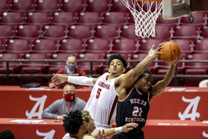 Alabama guard Jaden Shackelford (5) pressures Western Kentucky guard Kenny Cooper (21) as Cooper rebounds the ball during the second half of an NCAA college basketball game, Saturday, Dec. 19, 2020, in Tuscaloosa, Ala. (AP Photo/Vasha Hunt)