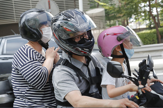 Family members wearing face masks leave after taking the COVID-19 test at a makeshift clinic in Seoul, South Korea, Thursday, Aug. 20, 2020. (AP Photo/Ahn Young-joon)
