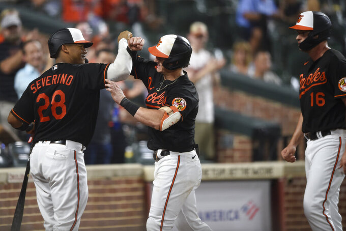 Baltimore Orioles' Austin Hays, center, is congratulated by Pedro Severino after hitting a two-run home run, also scoring Trey Mancini, right, in the fourth inning of baseball game against the Tampa Bay Rays, Friday, Aug. 27, 2021, in Baltimore.(AP Photo/Gail Burton)