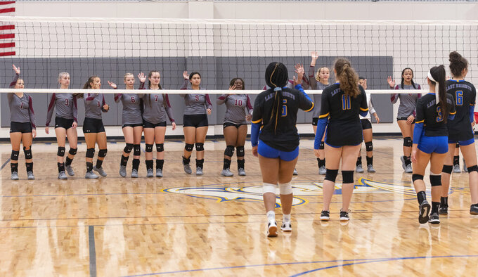Arp High School's varsity volleyball team approaches the net from a safe distance to wave to the Cumberland Academy team in lieu of shaking hands at the start of a match at Cumberland Academy on Tuesday, Aug. 25, 2020, in Tyler, Texas. (Sarah A. Miller/Tyler Morning Telegraph via AP)