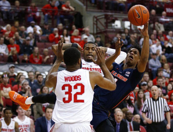 Illinois guard Trent Frazier, right, puts up a shot against Ohio State guard Keyshawn Woods, left, and forward Luther Muhammad during the first half of an NCAA college basketball game in Columbus, Ohio, Thursday, Feb. 14, 2019. (AP Photo/Paul Vernon)