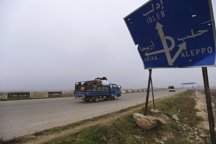 FILE - This Monday, Dec. 23, 2019, file photo, civilians ride in a truck as they flee Maaret al-Numan, Syria, ahead of a government offensive. The M5 highway, recaptured by President Bashar Assad's forces this week, is arguably the most coveted prize in Syria's civil war. The strategic highway is vital for Syria's  economy as well as for moving troops. (AP Photo/Ghaith Alsayed, File)