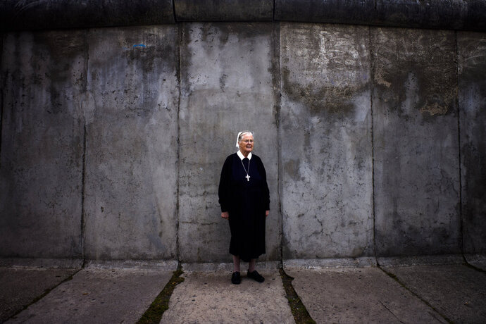 In this Sept. 18, 2019, photo, Sister Brigitte Queisser of the Lutheran Lazarus Order poses for a photo in front of concrete remains of the Berlin Wall during an interview with The Associated Press in Berlin. For many years, Sister Brigitte and other deaconesses lived in West Berlin across the street from the wall in the mother house of the Lutheran Lazarus Order, which ran a hospital where many of the people injured while escaping from East Berlin were treated. (AP Photo/Markus Schreiber)