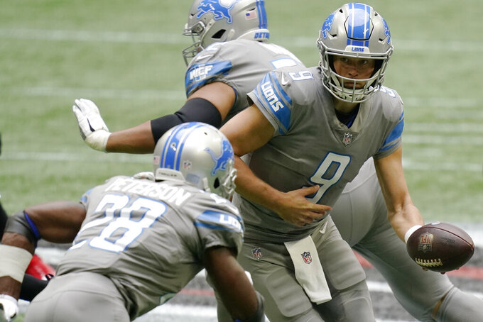 Detroit Lions quarterback Matthew Stafford (9) hands the ball off to Detroit Lions running back Adrian Peterson (28) against the Atlanta Falcons during the first half of an NFL football game, Sunday, Oct. 25, 2020, in Atlanta. (AP Photo/Brynn Anderson)