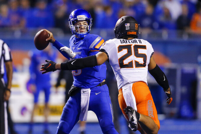 Boise State quarterback Hank Bachmeier (19) is pressured by Oklahoma State safety Jason Taylor II (25) during the second half of an NCAA college football game Saturday, Sept. 18, 2021, in Boise, Idaho. (AP Photo/Steve Conner)