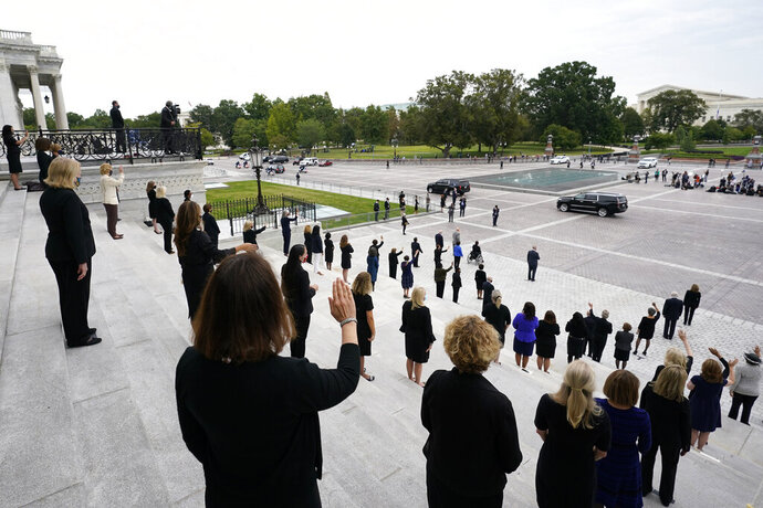 Female members of Congress stand on the steps of the U.S. Capitol and wave as the hearse carrying the flag-draped casket of Justice Ruth Bader Ginsburg departs after Ginsburg lied in state at the U.S. Capitol, Friday, Sept. 25, 2020, in Washington.(AP Photo/Alex Brandon, Pool)